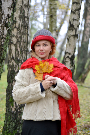 Portrait of the woman of average years with yellow maple leaves in hands