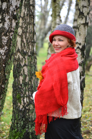 stole: Portrait of the joyful woman of average years in a red stole and a hat
