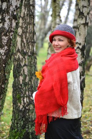 stole: Retrato de la mujer alegre de los años medios en una estola roja y un sombrero