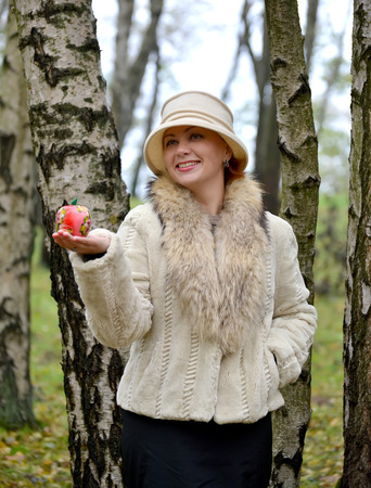 The joyful woman keeps decorative apple on a palm in a hat