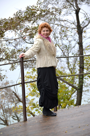 The cheerful woman of average years costs on the observation deck by the sea