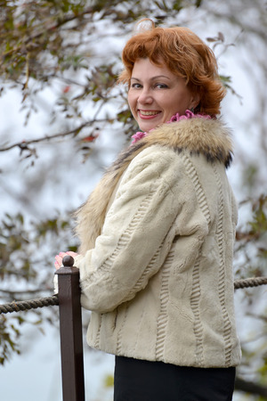 Portrait of the happy woman of average years in a light short fur coat
