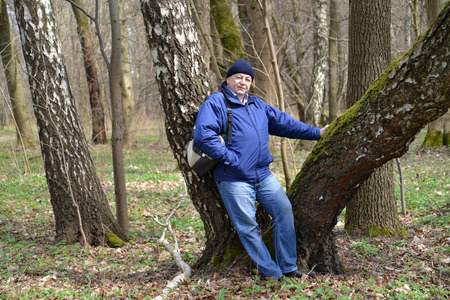 leaned: The elderly man costs having leaned against a birch in the spring wood Stock Photo