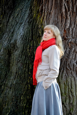 The young pensive woman costs sideways against the background of a tree Stock Photo