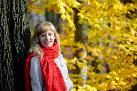 Portrait of the joyful young woman with a red scarf against the background of an autumn tree