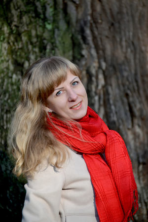 Portrait of the young fair-haired woman against the background of a tree Stock Photo