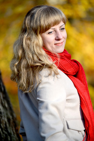 Portrait of the young woman with with looked down and a red scarf Stock Photo