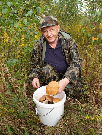 50 55 years: The joyful man puts a mushroom in a bucket Stock Photo