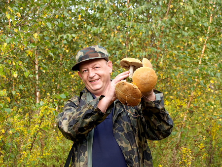 The cheerful man holds in hand mushrooms (focus on mushrooms)