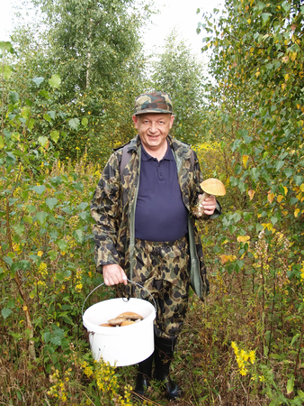 50 55 years: The man holds in hand a bucket with mushrooms in the wood