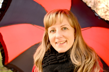Portrait of the young cheerful woman against the background of a black-red umbrella 写真素材