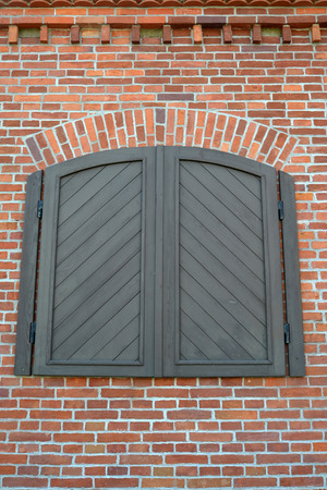 without window: Wooden sun blind on a red brick wall, imitation of a window Stock Photo