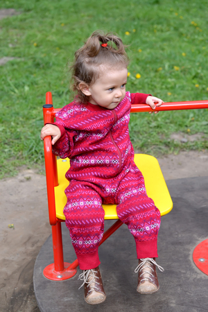 playground rides: The little girl rides a roundabout. Playground
