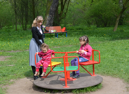 The young woman rolls two children on a roundabout in the park