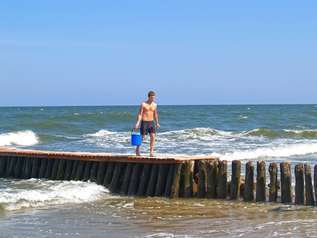 ZELENOGRADSK, RUSSIA - JULY 12, 2011: The young man goes on an old breakwater with a water bucket