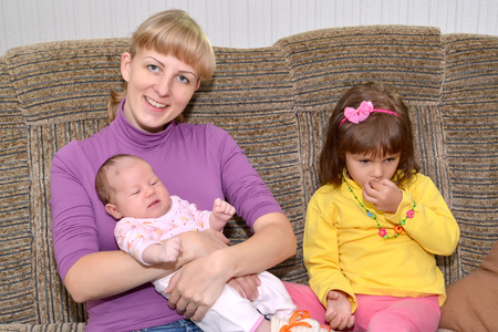 The young woman with the three-year-old daughter and the baby sits on a sofa Stock fotó - 74344760