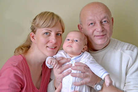 Young woman, grandfather and baby. Family portrait