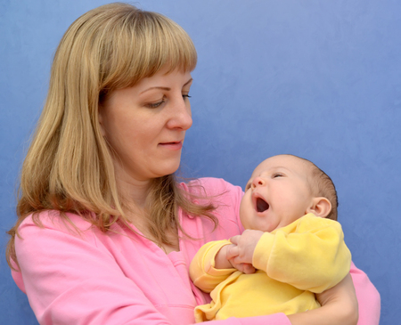 The yawning baby on hands at the young woman on a blue background Stock Photo