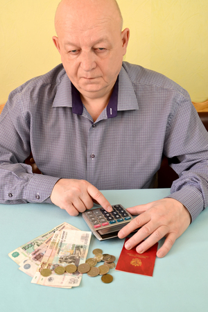 The pensioner thoughtfully counts money on the calculator Stock Photo