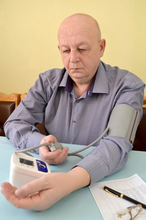 The elderly man measures pressure by an electronic tonometer semiautomatic device