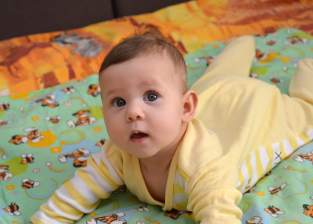 The baby with an open mouth lies on a stomach