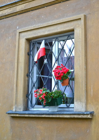 National flag of Poland and decorative flowers in a building window