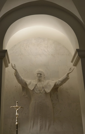 upraised: WARSAW, POLAND - AUGUST 23, 2014: A statue of the Pope John Paul II in a niche of a cathedral church of the Sacred Cross