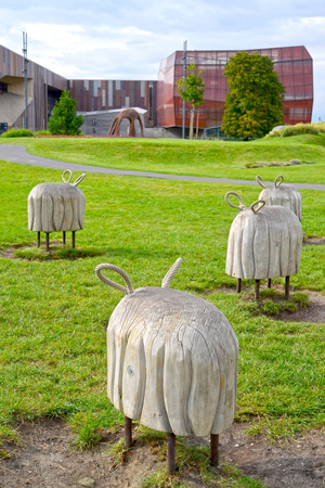 WARSAW, POLAND - AUGUST 23, 2014: Decorative wooden sculptures of sheep in the Park of openers against the background of the planetarium building. Center of Science of Copernicus