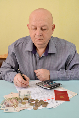 The pensioner counts cash expenditures on utility payments Stock Photo