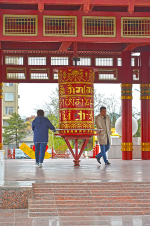 ELISTA, RUSSIA - APRIL 19, 2017: People spin a prayer wheel with a mantra of Ohms of Manya Padme Hum. Pagoda of Seven Days Editorial