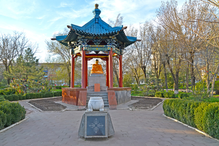 ELISTA, RUSSIA - APRIL 18, 2017: A rotunda arbor with Buddha Shakyamuni and a memorable sign in the square