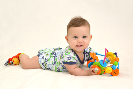 The amusing baby holds a toy on a light background