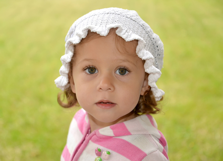 Portrait of the little surprised girl in the white Panamanian on a green background