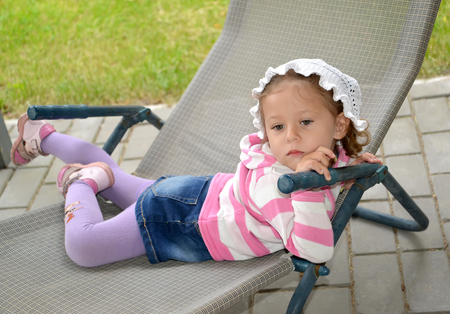 The little sad girl lies in a chaise lounge Stock Photo