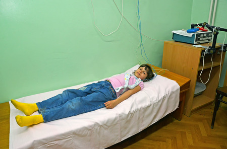 The sick girl adopts the procedure in a physiotherapeutic office. Treatment
