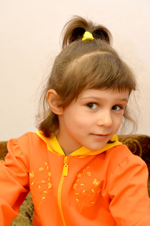 Portrait of the little girl in an orange jacket