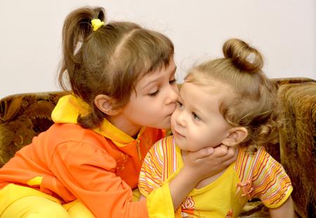 The girl kisses the younger little sister. Portrait