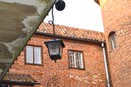 xv century: Decorative lamp against the background of a brick wall of the lock of the Teutonic Order. Poland, Kentshin