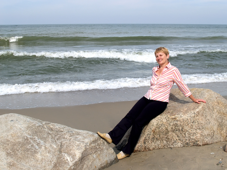 The woman of average years sits on a boulder. Coast of the Baltic Sea