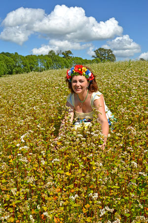 The joyful woman of average years with a wreath on the head in the blossoming buckwheat field