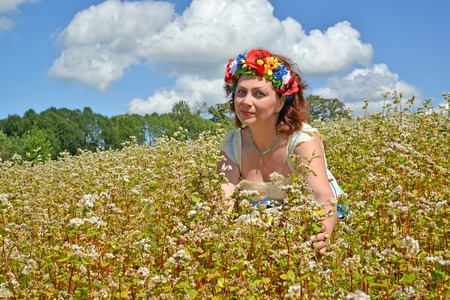 The woman of average years with a wreath on the head among the blossoming buckwheat