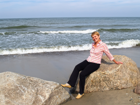 The cheerful woman of average years sits on a boulder. Coast of the Baltic Sea Stock Photo