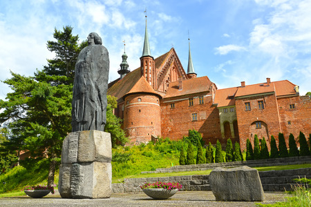 FROMBORK, POLAND - JULY 09, 2015: Monument to Nicolaus Copernicus and fragment of a cathedral complex