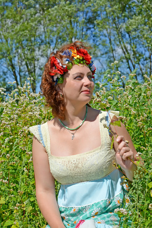 Portrait of the woman of average years with a wreath on the head against the background of the blossoming buckwheat Stock Photo