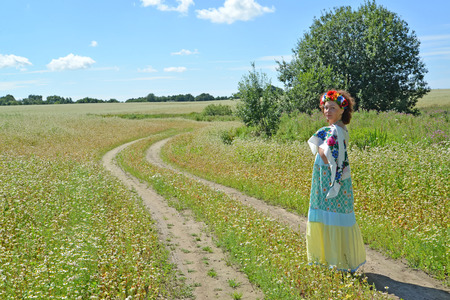 The woman with a wreath on the head goes on a path in the blossoming buckwheat field