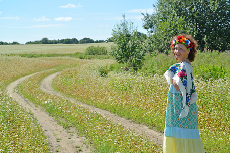 The cheerful woman with a wreath on the head goes on a path in the blossoming buckwheat field