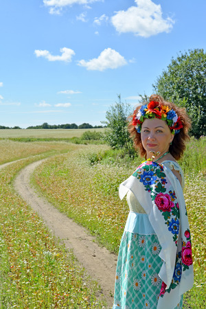 The womans portrait with a wreath on the head on the edge of the blossoming buckwheat field Stock Photo