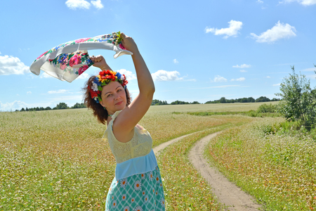 The woman with a wreath on the head holds a colorful scarf in the raised hands against the background of the blossoming buckwheat field