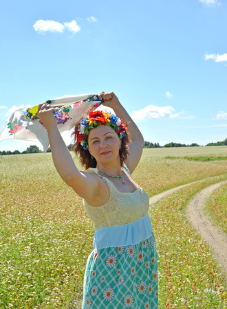 The mature woman with a wreath on the head holds a colorful scarf in the raised hands against the background of the blossoming buckwheat field Stock Photo