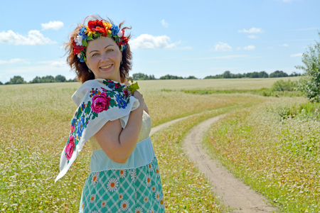 The joyful woman with a wreath on the head against the background of the blossoming buckwheat field